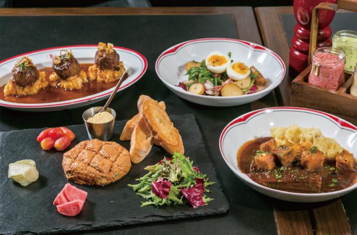 ベルギーの伝統料理「L'AMÉRICAIN BEEF TARTARE」(左手前)や煮込み料理「CARBONNADE À LA FLAMMANDE」(右手前)など他では食べられない逸品がズラリ
