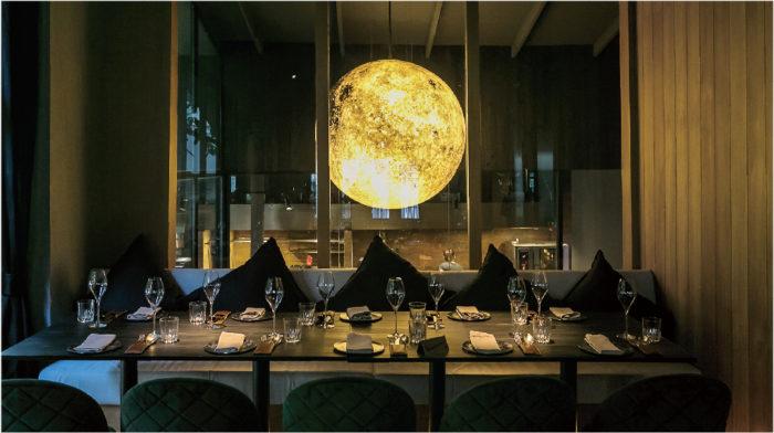満月をモチーフにした照明が柔らかく店内を灯し、洗練されたディナータイムを演出する
