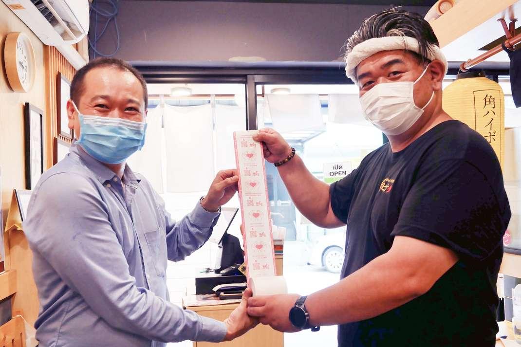 เราสนับสนุนกิจการร้านอาหารญี่ปุ่นของลูกค้าอย่างเต็มที่ด้วยม้วนใบเสร็จจากบริษัทเรา (ภาพถ่ายร่วมกับคุณฮาเสะกาวะ CEO ของร้าน Hinata Kushiyaki Kushiage)