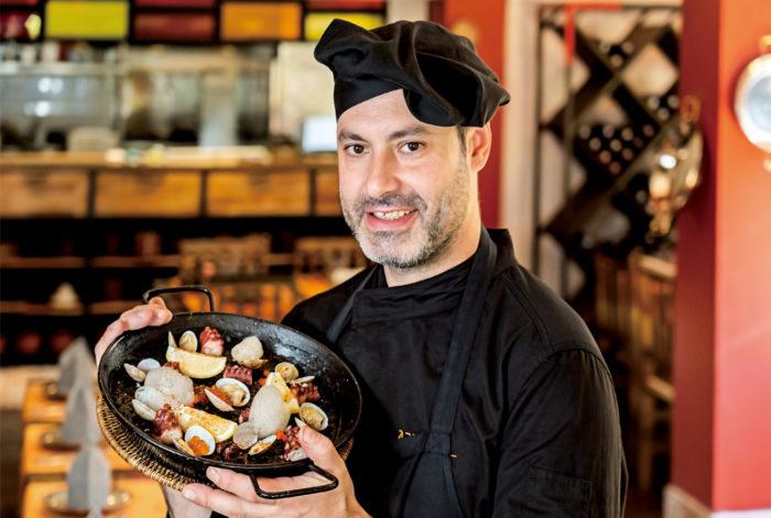 当店で一番人気のイカスミのパエリアです。お米の黒さに驚かれる方もいらっしゃいますが、魚介の旨みと特製スープをたっぷりと吸っパエリアは香ばしく、繊細かつ奥行きのある味わいが特徴です。肉厚なタコや日本産のイクラも食感と彩りを添えます。自家製のサングリアやこだわりのスペイン産ワインと共にぜひご賞味あれ!