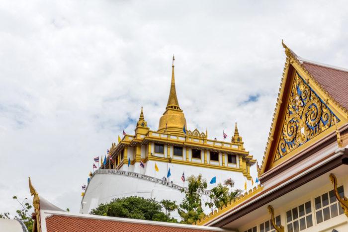 Wat Saket 344段の螺旋階段を上り、アユタヤ時代の「プー・カオ・トーン(黄金の仏塔)」を再現した小高い丘の頂上へ。バンコクの街並みを一望することができ、夕日に染まる黄金の大仏塔(チェディ)の美しさは圧巻です。仏塔内には仏舎利(釈迦の遺骨)が納められています。