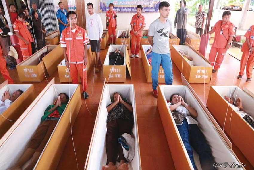 棺の中に横になりながら瞑想する人々