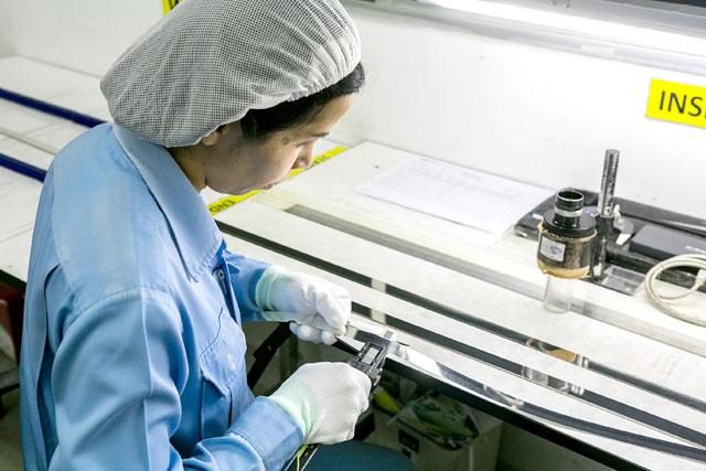 ฝ่ายควบคุมคุณภาพกำลังทำการตรวจวัดคุณภาพของผลิตภัณฑ์